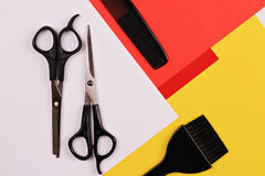 Scissors,comb and brush for hair coloring on on colorful, simple, minimalistic, geometric background. Hairdresser salon concept. H Stock Photo