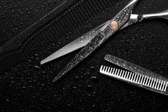 Scissors covered with water droplets. Barber tool royalty free stock photos