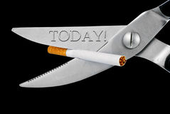 Scissors cut a cigarette. Isolated on a black background Royalty Free Stock Photography