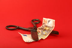 Scissors cut Euro banknote over red background Stock Photos