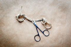 Scissors cut the knot on rope at background kraft paper Royalty Free Stock Images