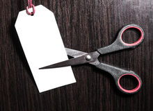 Scissors cut paper white price tag on a brown wooden background. Stock. Discounts. Benefit. marketing concept.  Stock Image