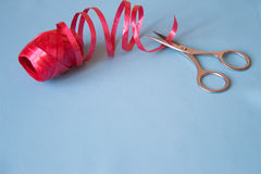 Scissors cut the red ribbon on blue background Stock Photos