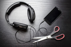 Scissors cut the wire from the headphones, leading to the phone, and thus stop the very loud illegal pirated music Stock Images