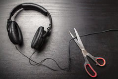 Scissors cut the wire from the headphones, and thus stop the very loud illegal pirated music Royalty Free Stock Photos