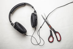 Scissors cut the wire from the headphones, and thus stop the very loud illegal pirated music Stock Photo