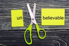 Scissors cut the word unbelievable. concept believable. cuts the word. `un. `I can, goal achievement, potential, overcoming Stock Photography