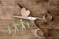 Scissors with cutout paper family and heart Stock Photos