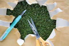 Scissors and cutter on torn paper Royalty Free Stock Photography