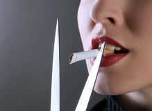 Scissors cutting. A female is cutting cigarette in her mouth Royalty Free Stock Image