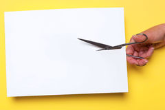 Scissors cutting blank paper. Photo of a womans hand cutting through a blank piece of white paper with chrome scissors on a yellow background, add your own image stock images