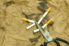 Scissors are cutting a cigarette Royalty Free Stock Images