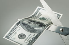 Scissors cutting a dollar bill in half. Money being cut showing cutbacks or wasteful spending Stock Images