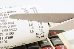 Scissors cutting receipt from shop. Economy concept with scissors cutting receipt from shop Royalty Free Stock Images