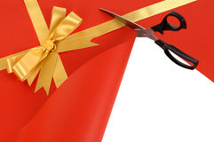 Scissors cutting red gift wrap paper revealing white background Royalty Free Stock Photo