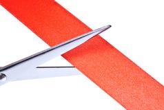 Scissors cutting red ribbon Royalty Free Stock Photos