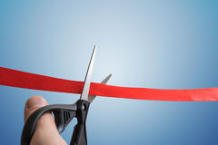 Scissors are cutting red ribbon. Opening ceremony concept. Isolated on blue background Stock Photo