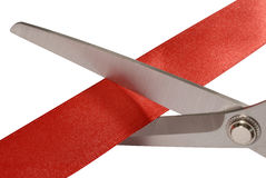 Scissors cutting red ribbon or tape, isolated on white, close up Stock Images