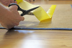 Scissors Cutting Rug Grip Tape. Male caucasian hands with black handle stainless steel scissors cutting to size a strip of yellow anti-slip rug grip tape Stock Photo