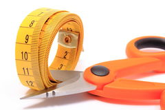 Scissors cutting tape measure on white background Royalty Free Stock Photos