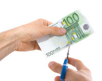 Scissors and euro. A bill of 100 euro being cut in two with scissors isolated on white background royalty free stock photography