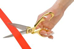 Scissors in a female hand cut a red tape Stock Image