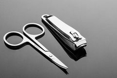 Scissors and forceps for caring for hands with reflection. Scissors and forceps for caring for hands on a black background with reflection Royalty Free Stock Images
