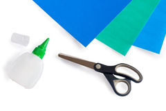 Scissors, glue and color paper on a white background Royalty Free Stock Photos