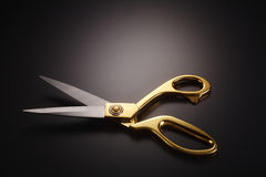 Scissors. Golden scissors on the gray background Stock Images