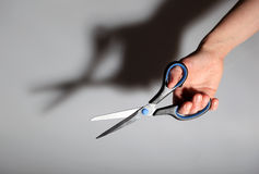 Scissors in hand. On gray background with shadow Royalty Free Stock Photos