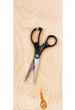 Scissors hanging on a wooden board Royalty Free Stock Images