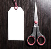 Scissors lying near empty labels on brown wooden background.Blank tag. Royalty Free Stock Photos