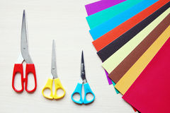 Scissors and many sheets of multicolored paper Stock Photos