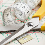 Scissors and measuring tape on pattern Royalty Free Stock Photos