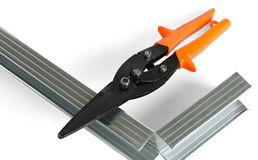 Scissors on metal and directing for gypsum cardboard installation. Scissors on metal and the iron directing lie on a light surface Stock Image