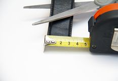 Scissors, meter, piece of leather material. He measured three times, and once he cuts it.nOn the white background is:Scissors, meter, piece of leather material stock photo