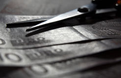 Scissors on Money. In silver (cutting costs Stock Photo