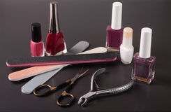 Scissors, nail files and clippers manicure with polish bottles on a dark background Royalty Free Stock Image
