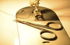 Scissors and needle of sewing machine in a background Stock Photography