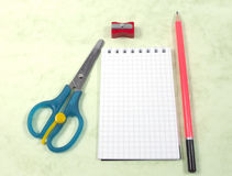 Scissors, notebook, pencil and pencil sharpeners. On patterned background Royalty Free Stock Photos
