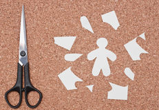 Scissors with paper man and parts on cork Stock Image