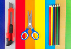 Scissors, pencils and cutter on colored paper Royalty Free Stock Images