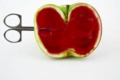 Scissors penetrate apple jelly Royalty Free Stock Photos