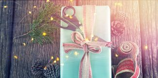 Scissors, pine cones, leaves and ribbon with wrapped gift box on wooden table Stock Image