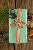 Scissors, pine cones, leaves and ribbon with wrapped gift box on wooden table Royalty Free Stock Image