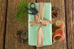 Scissors, pine cones, leaves and ribbon with wrapped gift box on wooden table Stock Photo