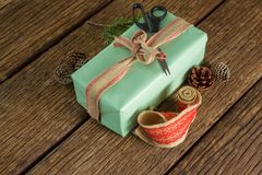 Scissors, pine cones, leaves and ribbon with wrapped gift box on wooden table Royalty Free Stock Photos