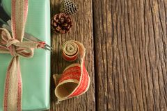 Scissors, pine cones and ribbon with wrapped gift box on wooden table Stock Photo