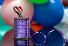 Scissors and purple washi tape at blurred multicolored balloons. copy space. selective focus. handiwork and art creativity. for de royalty free stock photography
