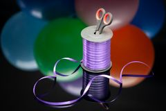 Scissors and purple washi tape at blurred multicolored balloons. copy space. selective focus. handiwork and art creativity. royalty free stock image